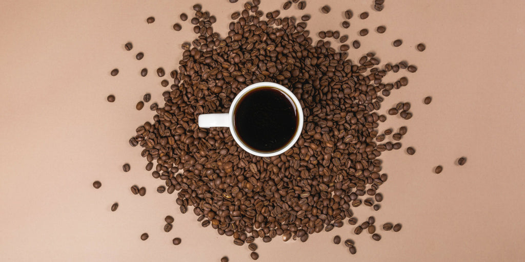 Coffee beans spread around a mug of coffee