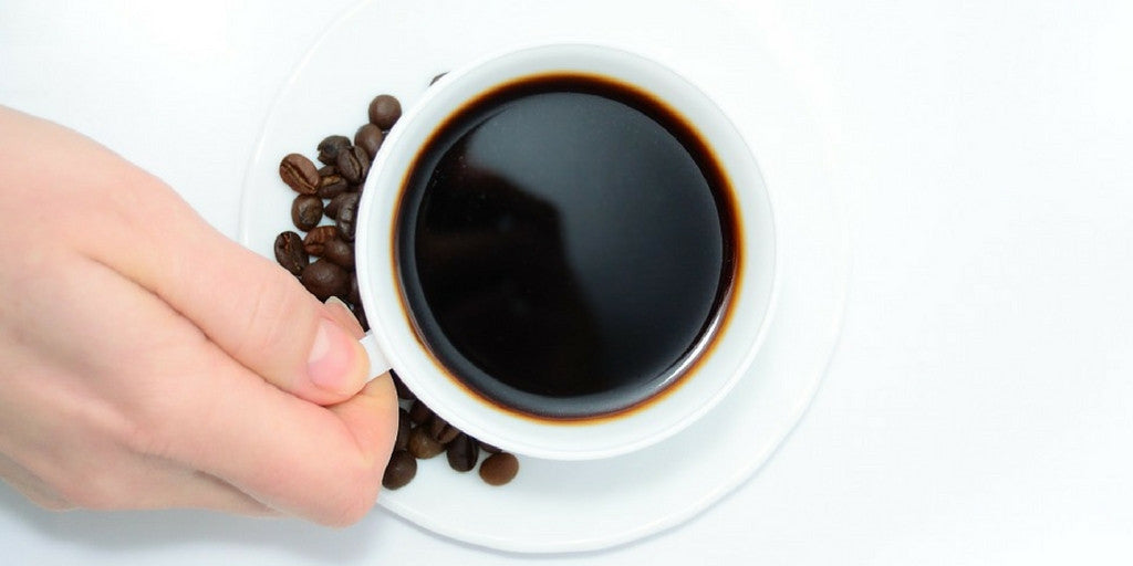 Hand holding a cup of coffee sitting on a plate with coffee beans