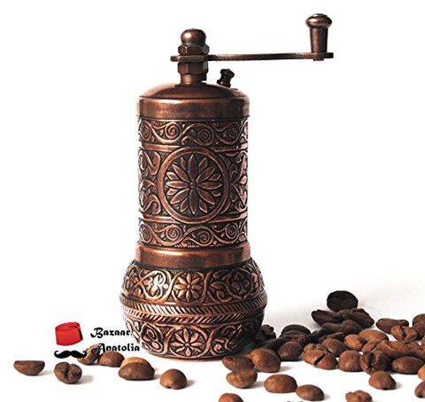 Turkish coffee grinder surrounded by beans