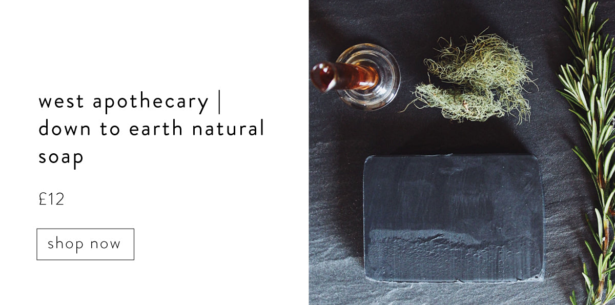 West Apothecary down to Earth natural soap. Black bar of soap on slate background next to a sprig of Rosemary.