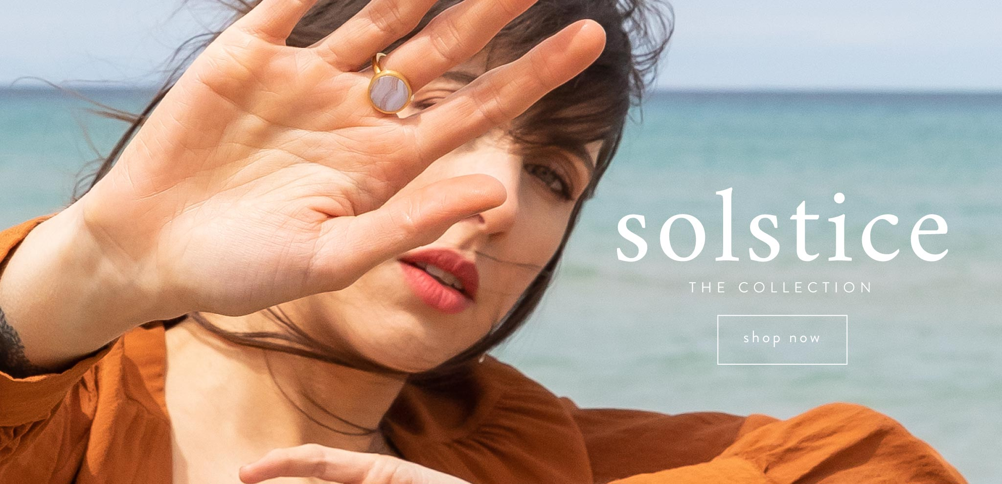 Woman wearing the Wanderlust Life Solar ring in blue Lace agate from the Solstice collection - stood in front of the sea