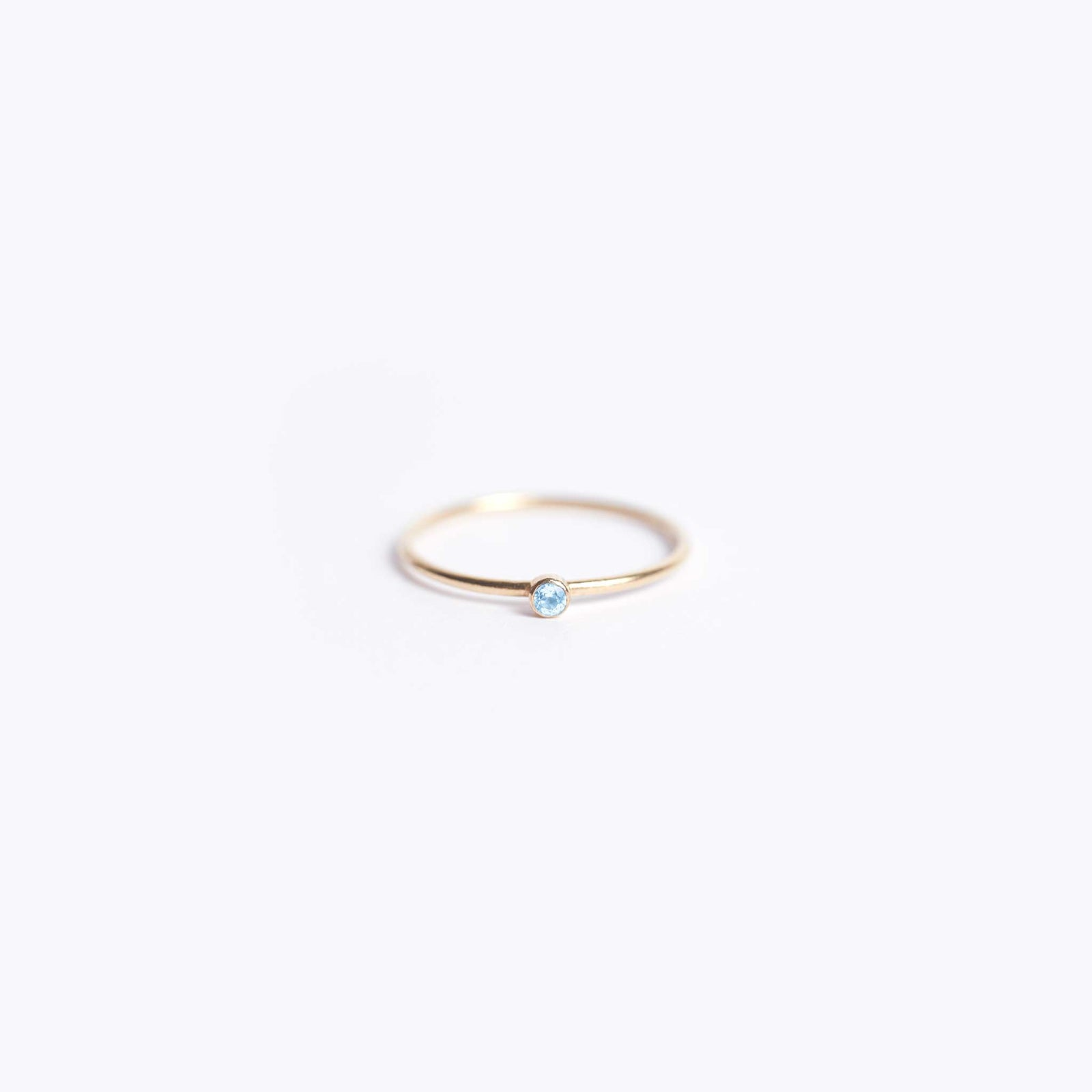 Wanderlust Life Ethically Handmade jewellery made in the UK. Minimalist gold and fine cord jewellery. november birthstone, fine gold blue topaz ring