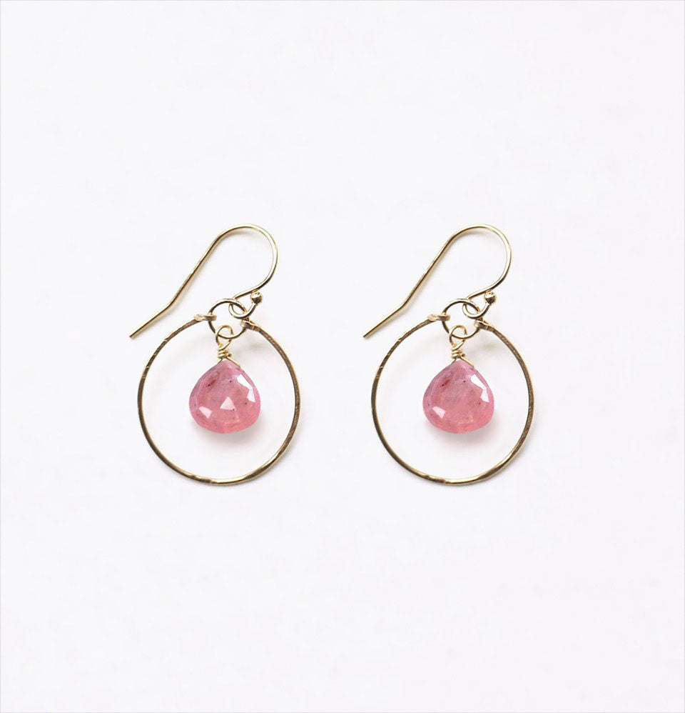 A 14k gold filled hammered hoop earring with a suspended pink jasper faceted semi precious gemstone