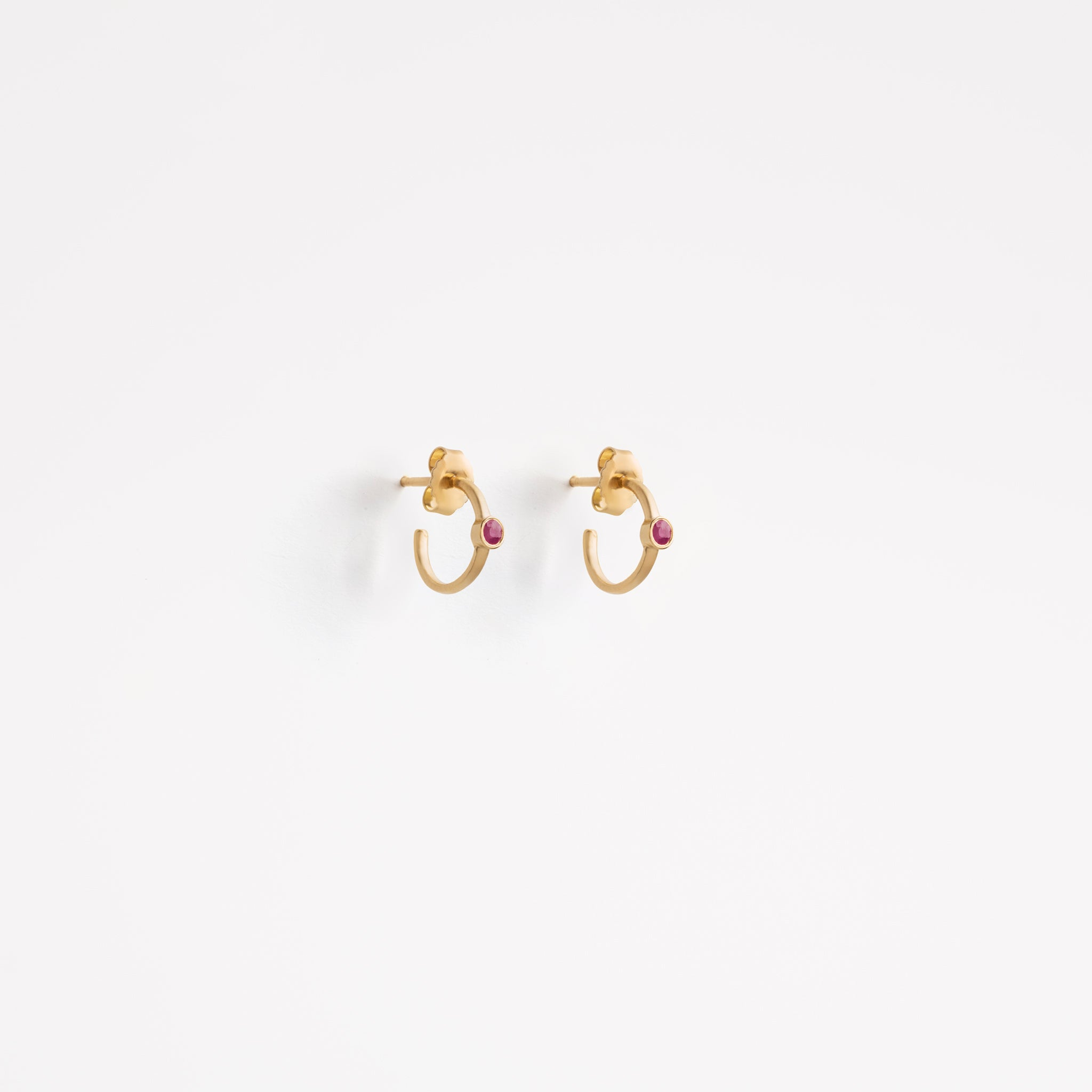 Wanderlust Life small gold huggie hoops set with semi precious ruby gemstones. Perfect gold hoop for stacking and layering. Wanderlust Life jewellery designed in the UK.