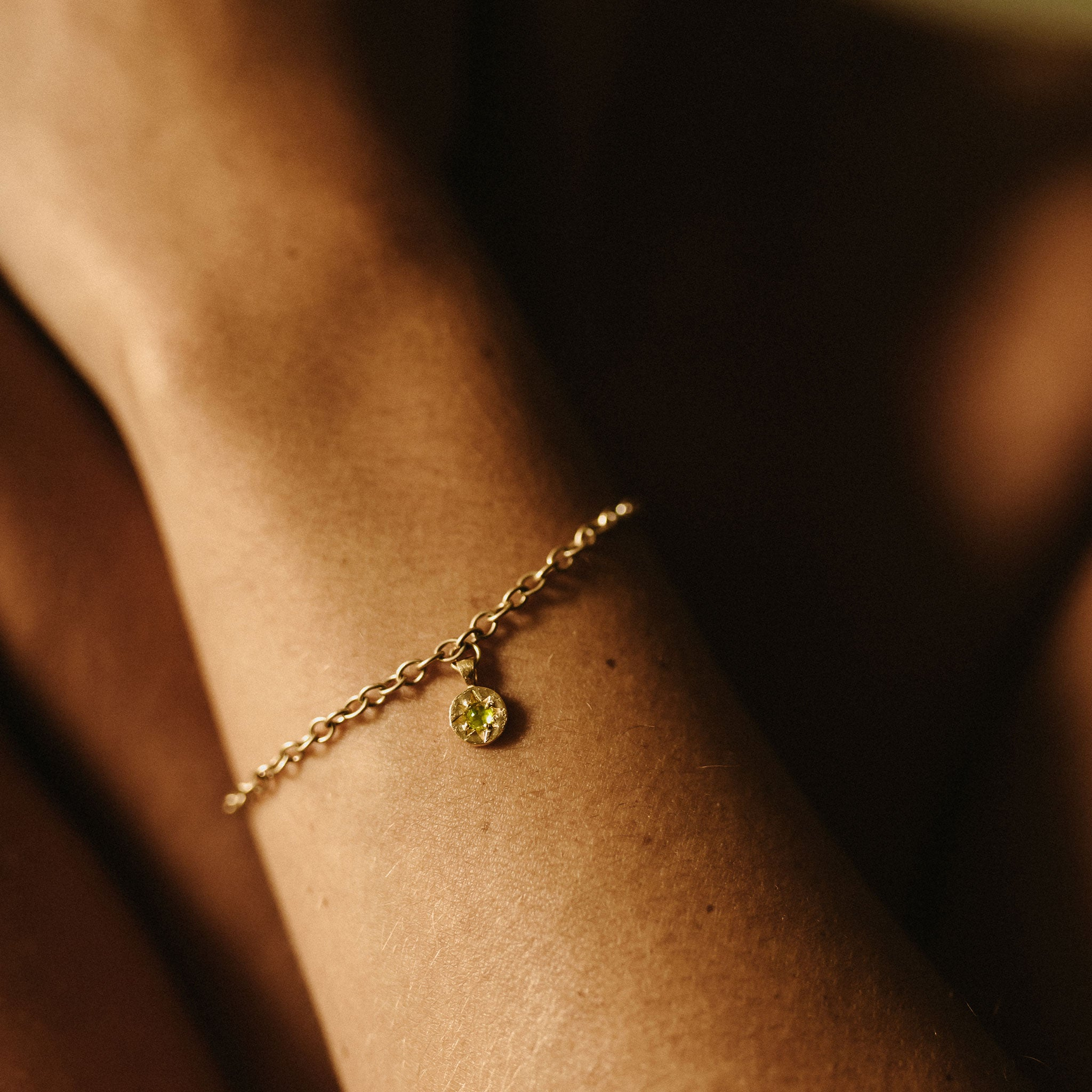 Wanderlust Life August birthstone 14k gold fill charm bracelet featuring semi precious peridot gemstone symbolising the month of August. August birthstone gold bracelet available in small 6.5