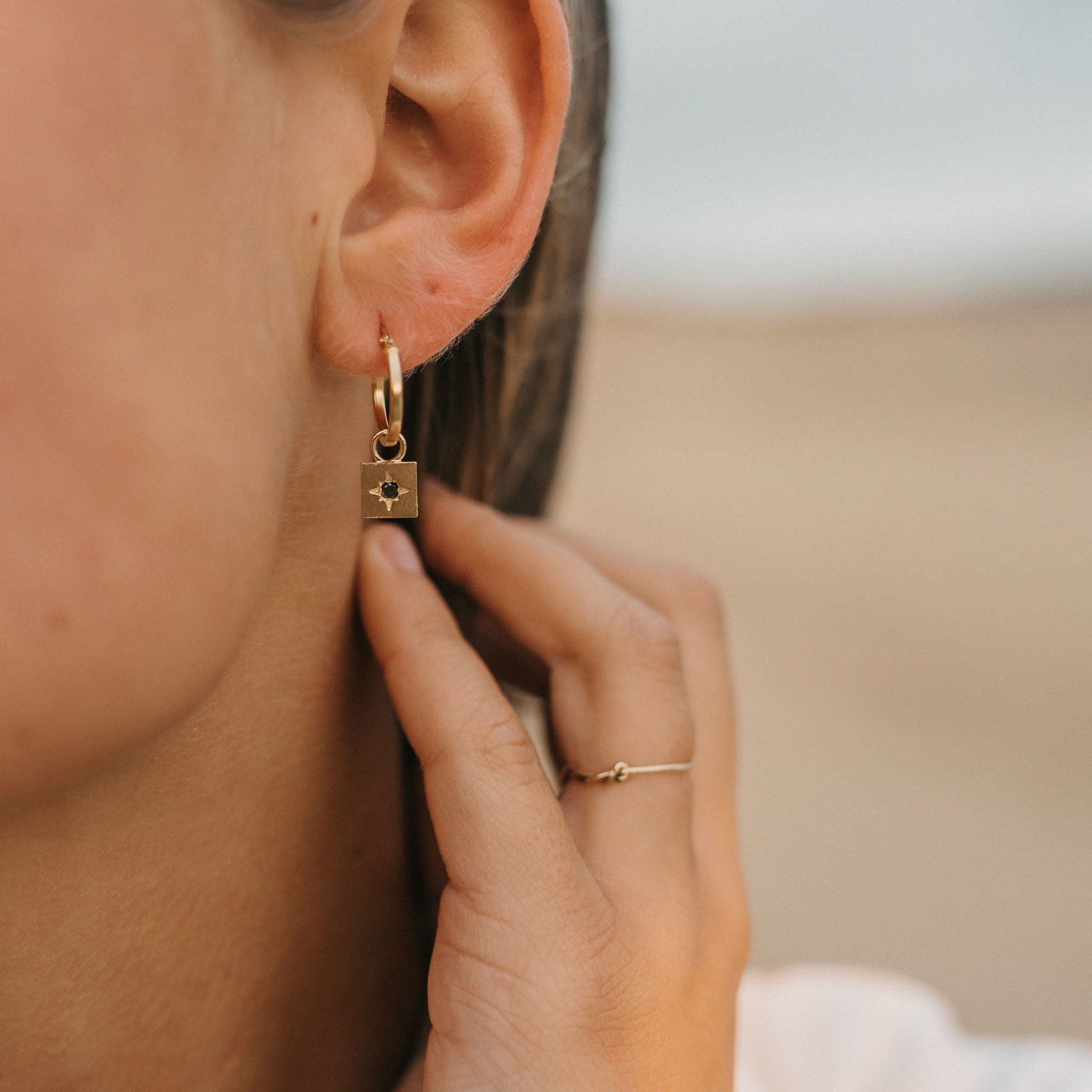 Wanderlust Life jewellery, gold hoop earring with black diamond. Black diamond gemstone falling from a 14k gold fill hoop. Wanderlust Life jewellery handmade in the UK.