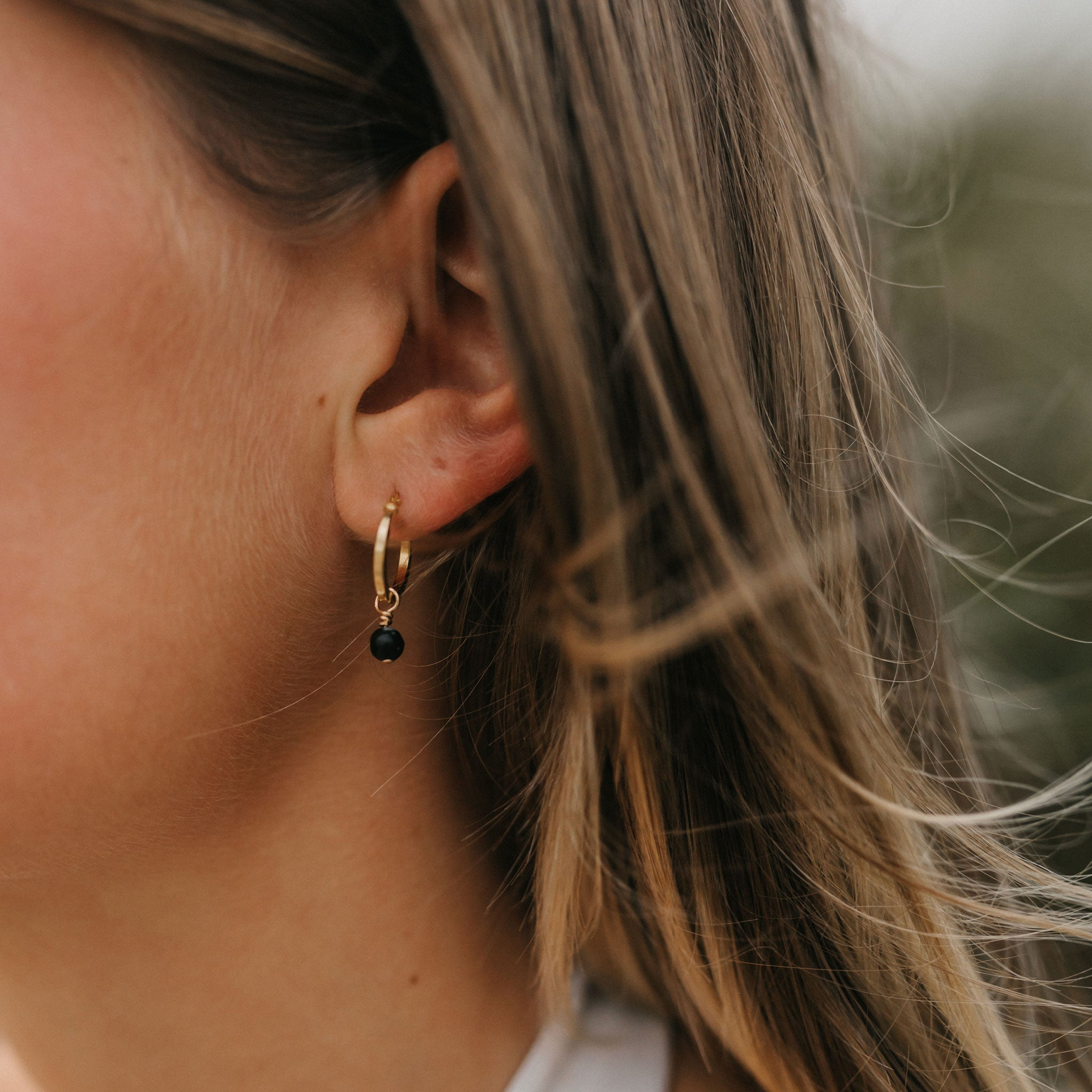 Wanderlust Life jewellery, 14k gold fill creole hoop earrings with semi precious black obsidian gemstone. Wanderlust Life jewellery handmade in Devon, UK.