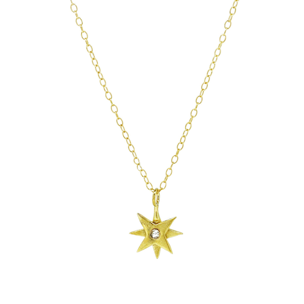 gold star necklace set with a white sapphire