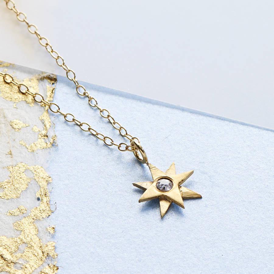 gold tiny star necklace set with a white sapphire