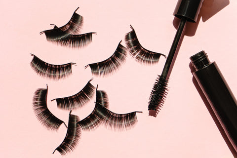 Five sets of false lashes on a pink background next to a tube and wand of mascara. Cartel Lash