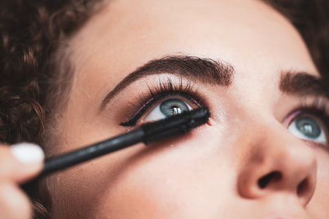 Woman wearing make up putting on specially formulated mascara for lash extensions. Cartel Lash
