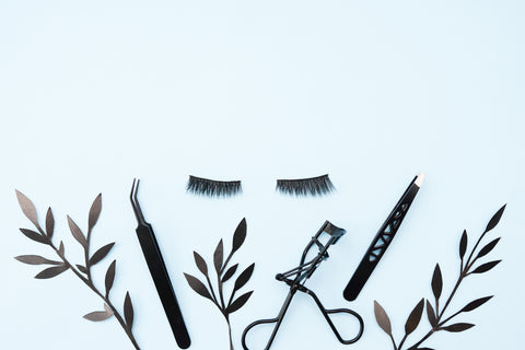 Black false lashes strips set with curler and tweezers on blue background decorated with black branches