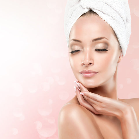 Woman wearing towel on head with clear skin, make up and lash extensions. Cartel Lash