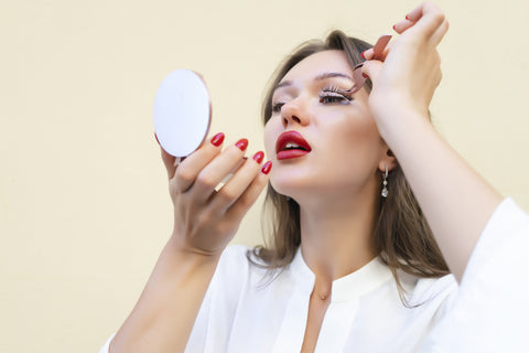 woman with short brown hair and red lipstick holding a mirror and applying false lashes. Cartel lash