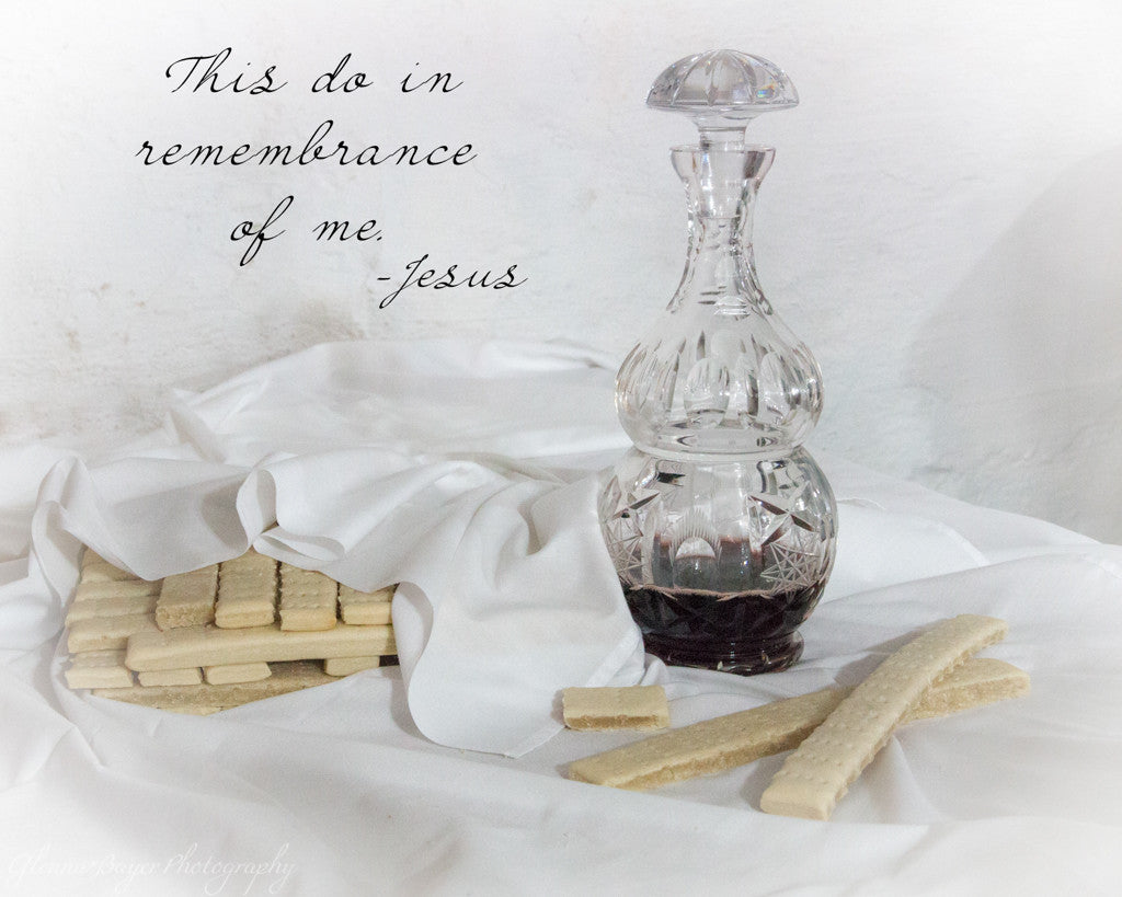 Unleavened communion bread under white linen cloth and wine in crystal decanter, with scripture verse