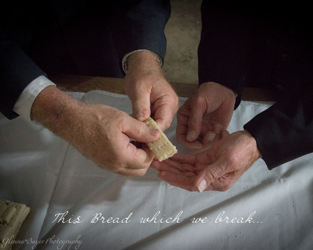 Men's hands breaking communion bread with scripture verse