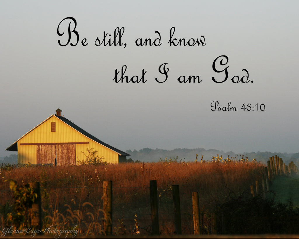 Old sunlit barn in field with scripture verse
