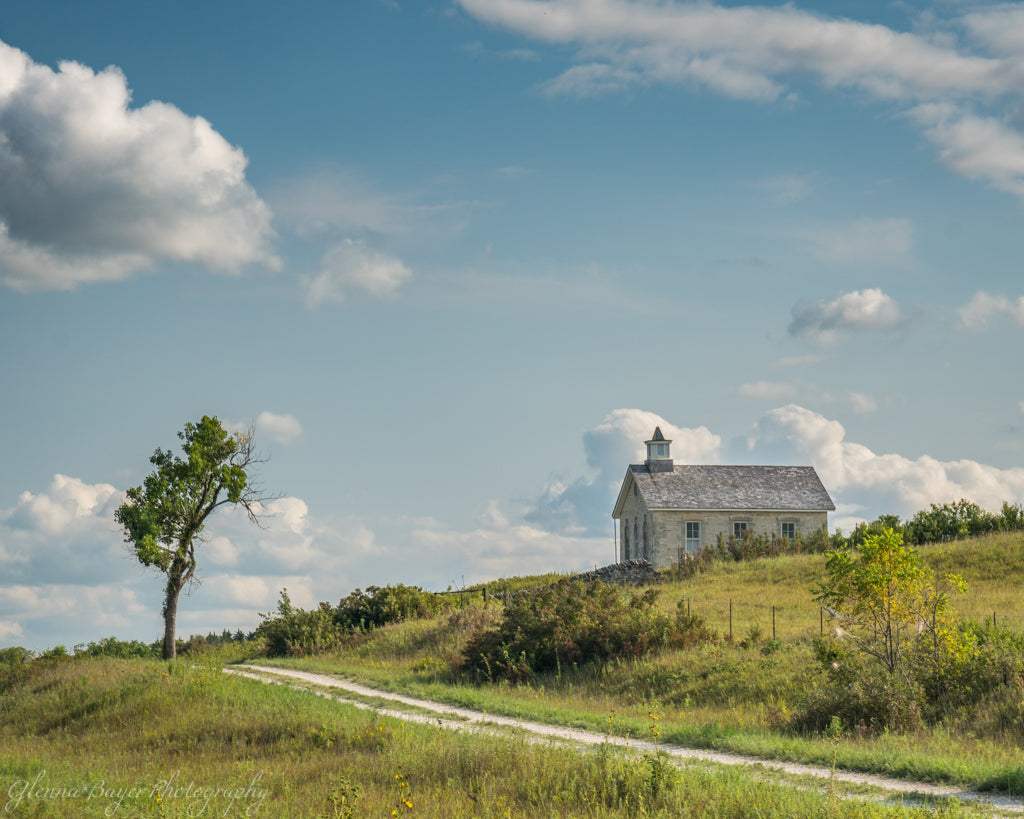 Old single room schoolhouse with gravel road and lone tree in the Flint Hills of Kansas