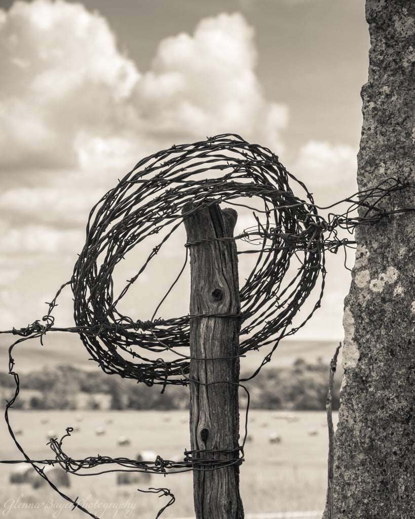 Barbed wire wrapped around post in Flint Hills, Kansas