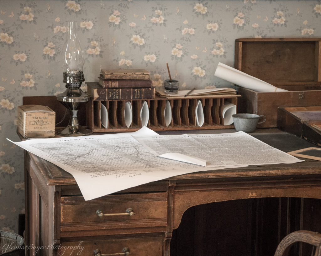 Old vintage desk with map, oil lamp, and writing quill in Flint Hills, Kansas