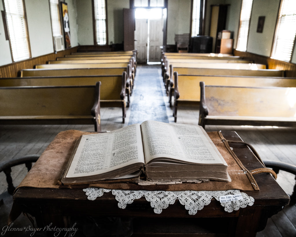 Old church with wooden pews and an open bible on the pulpit