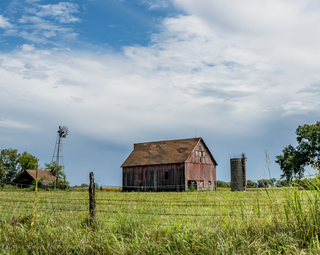 Old farm with wood barns and windmill during summer time in Kansas