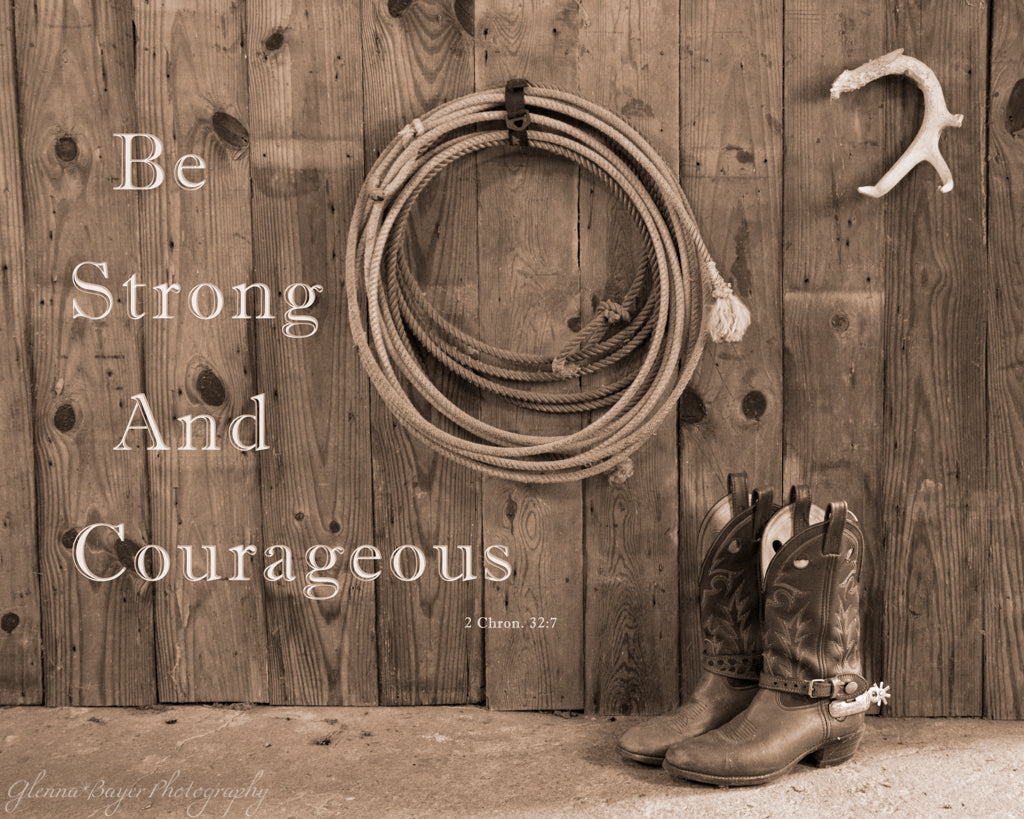 Cowboy boots and lasso rope against wooden barn wall with scripture verse