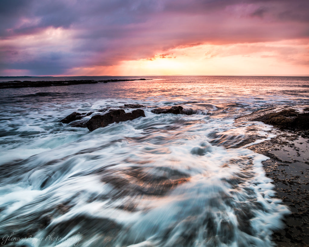 Sunrise over Jervis Bay and waves crashing over rocks in Australia