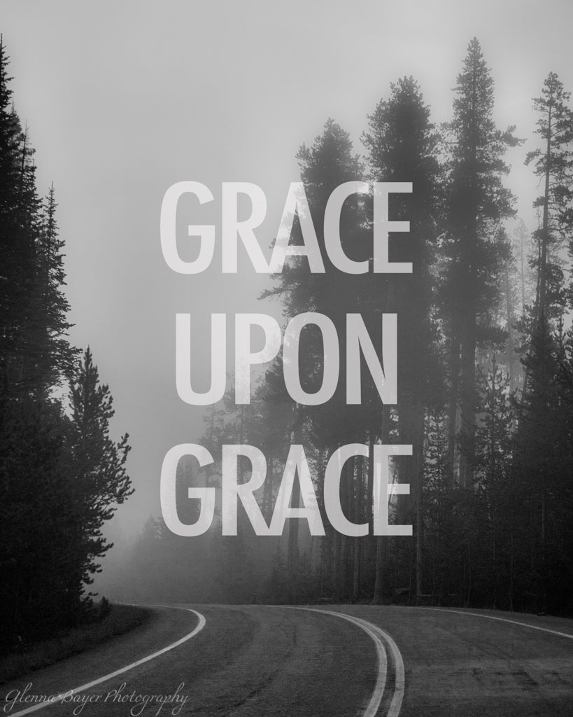 "A bend in the road through foggy trees in black in white with words ""Grace Upon Grace"""