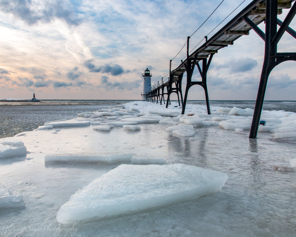 Manistee Lighthouse on Lake Michigan during winter with ice chunks
