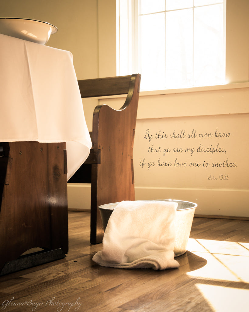 Footwashing tub and towel beside church bench with scripture verse