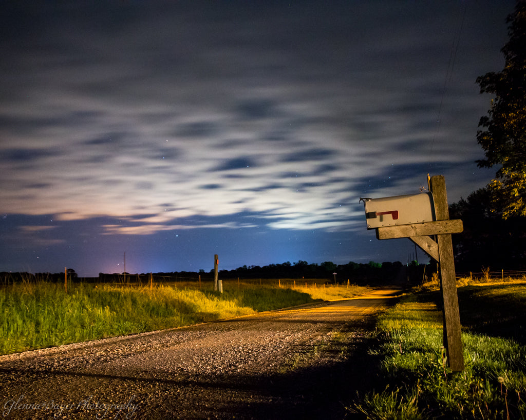 Mailbox beside gravel road and a cloudy night sky in Kansas