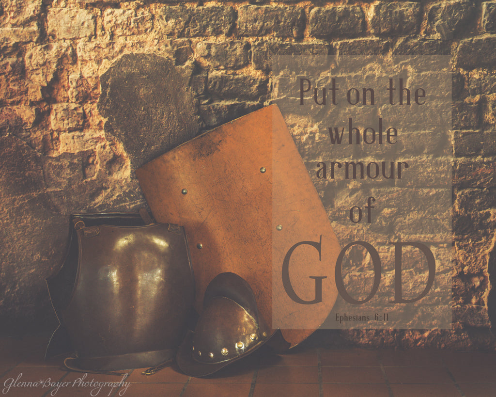 Shield, breastplate, and helmet leaning against brick wall with scripture verse about amour of God