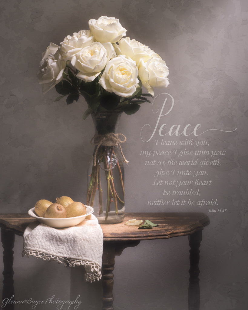 Still life of a white rose bouquet, kiwis in bowl, and white cloth on end table with scripture verse
