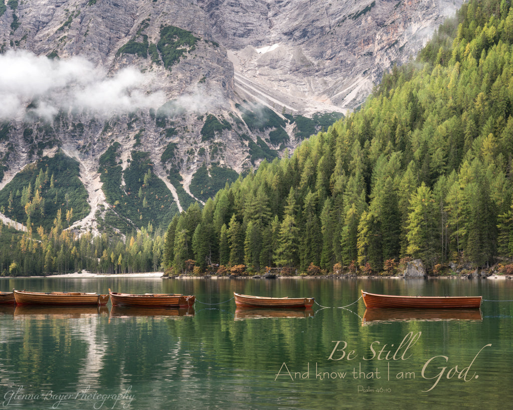 Canoes lined across Lake Braies in Dolomites, Italy with scripture verse