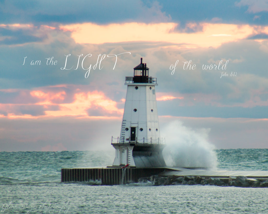 Wave crashing into Ludington Lighthouse on Lake Michigan during pink sunset with scripture verse