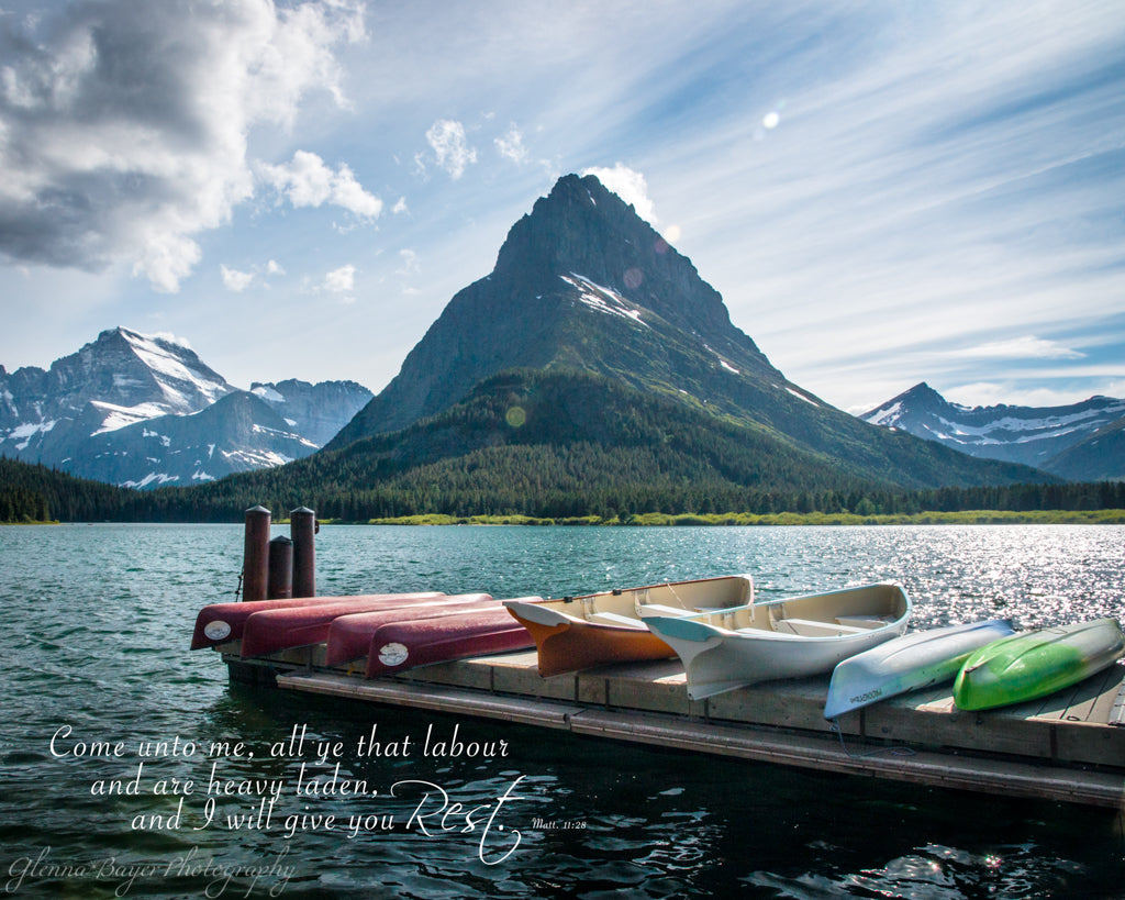 Canoes on dock at Lake McDonald in Glacier National Park with scripture verse