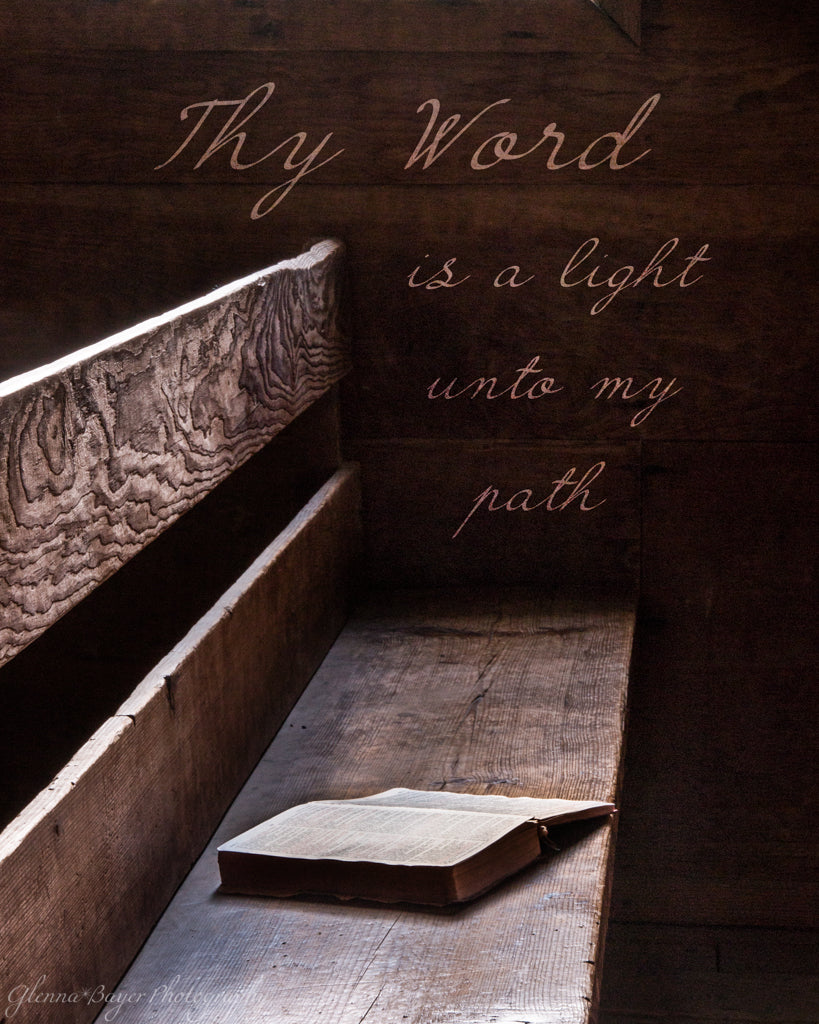 Old Bible lying on wooden bench with scripture verse.