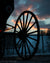 Silhouette of Amish buggy wheel during sunset