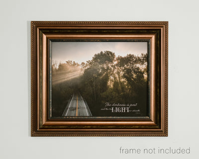 framed print of Arial of road going into woods and light shining through trees