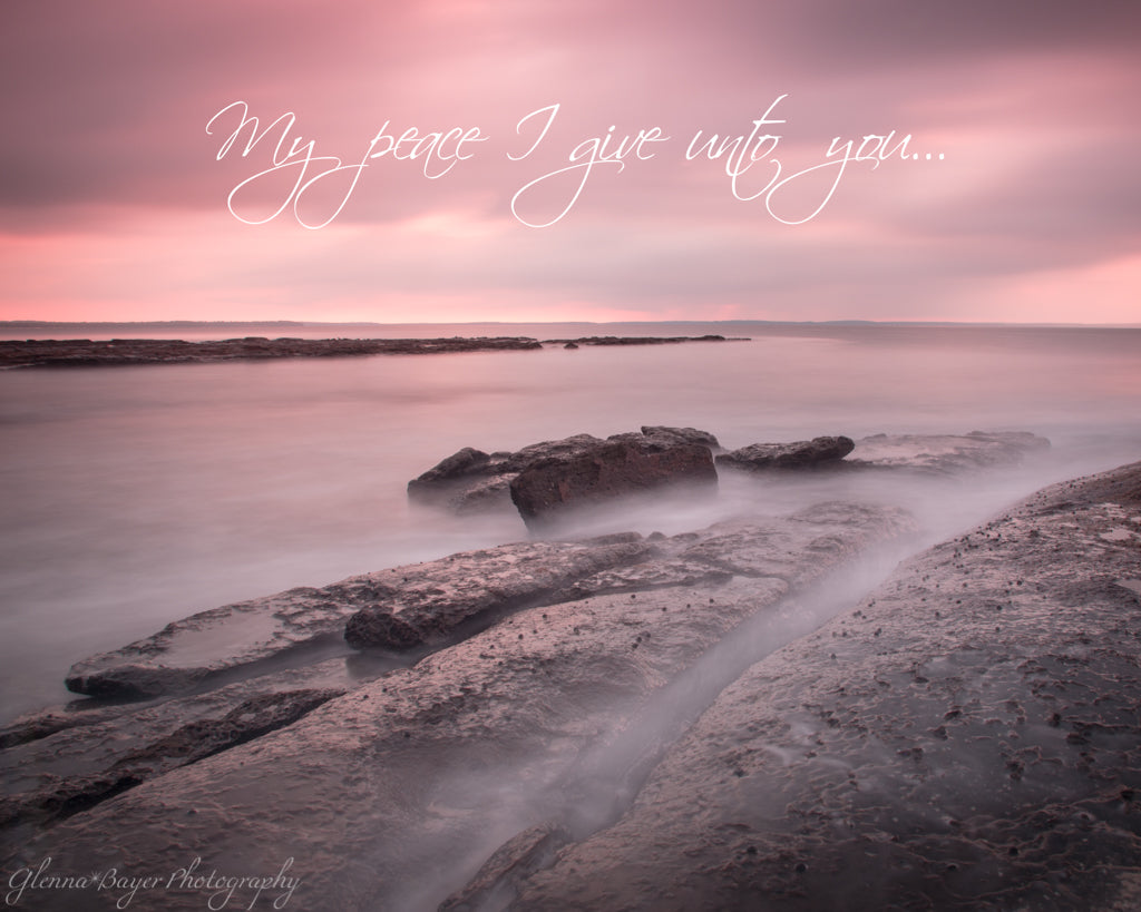 Pink sunrise and ocean flowing over rocks in Jervis Bay, Australia with scripture verse