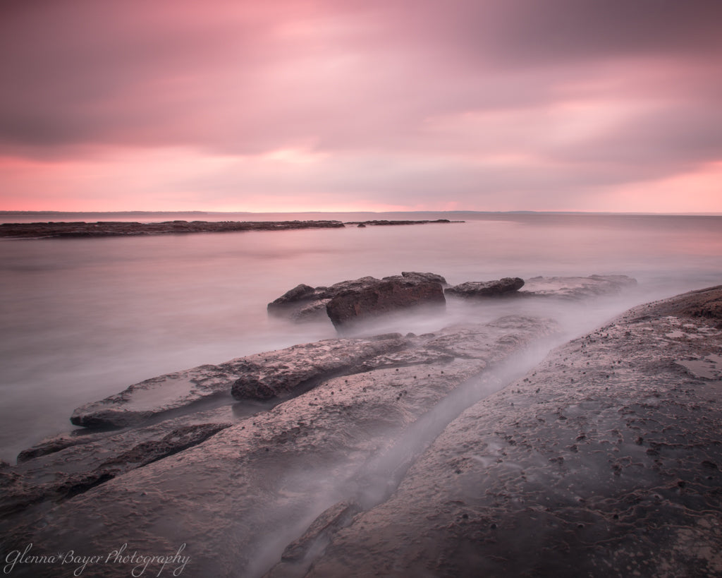 Pink sunrise and ocean flowing over rocks in Jervis Bay, Australia