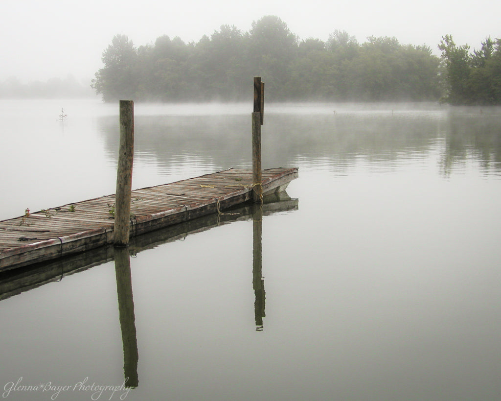 Old wooden dock over a lake on a foggy, gray morning.