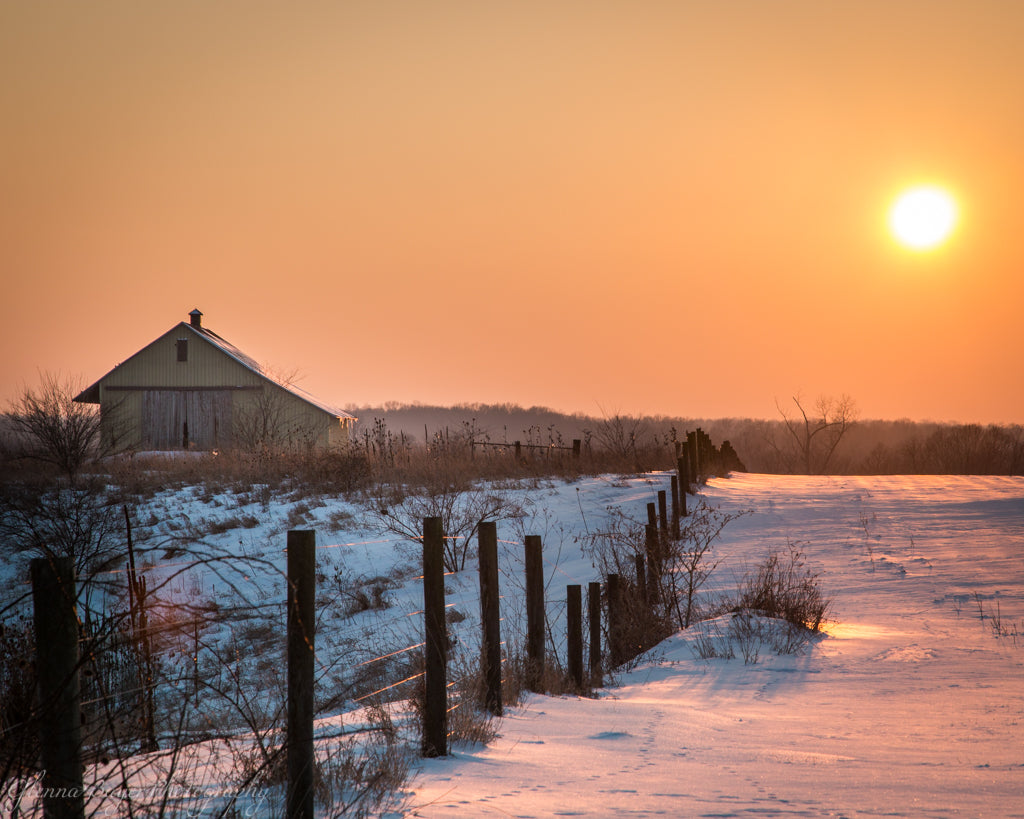 Old barn and fence row in snow with orange sunset