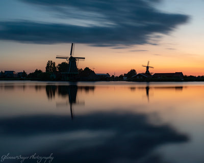 Orange sunrise and silhouettes of Holland windmills in Zaanse Schans