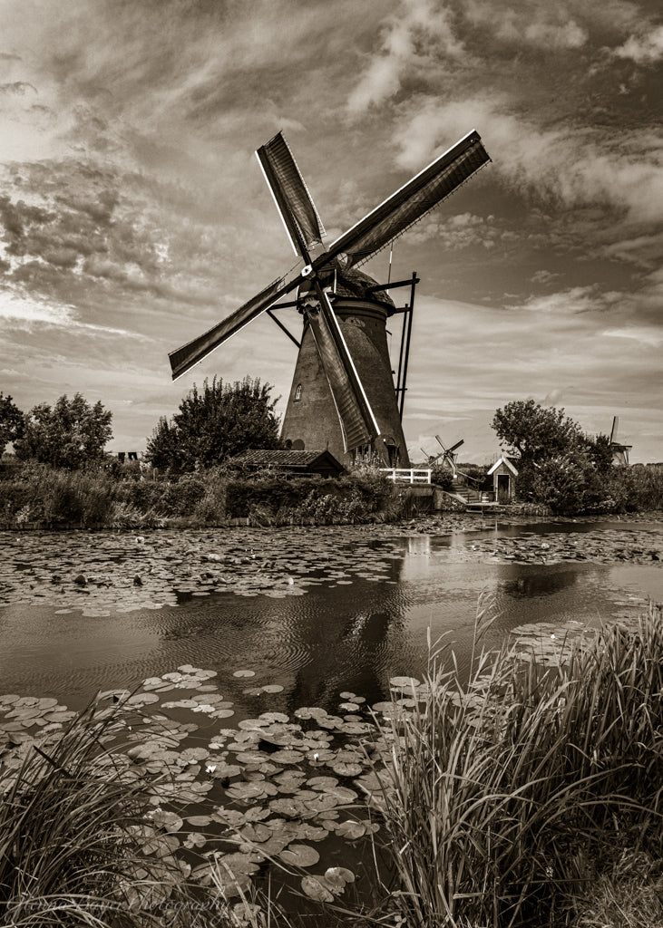 Holland windmill by canal in sepia