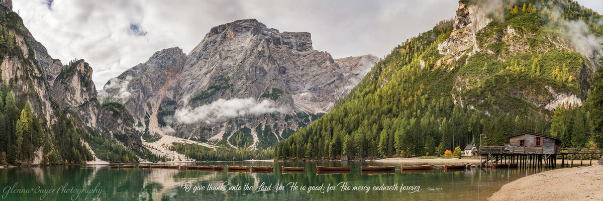 Panorama of canoes lined across Lake Braise in Dolomites, Italy with scripture verse