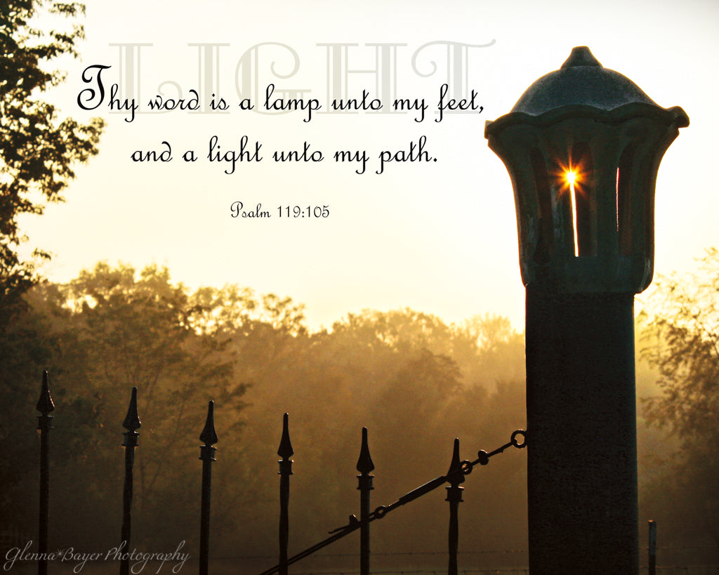 Silhouette of lamp post with sunburst in orange foggy morning light with scripture verse