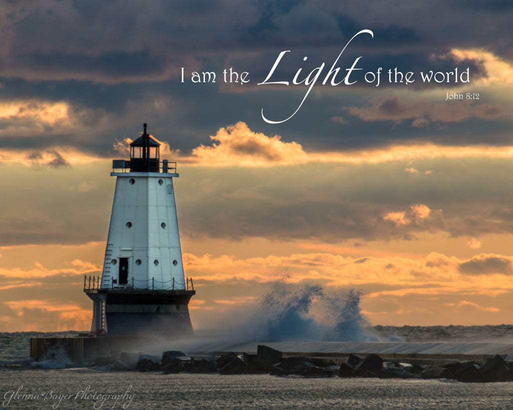 Wave crashing into Ludington Lighthouse on Lake Michigan during orange sunset with scripture verse