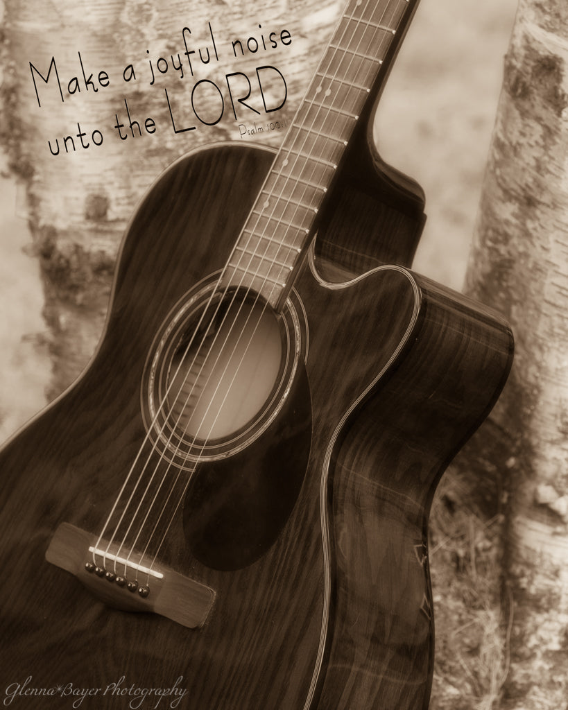 Acoustic guitar leaning against tree with scripture verse